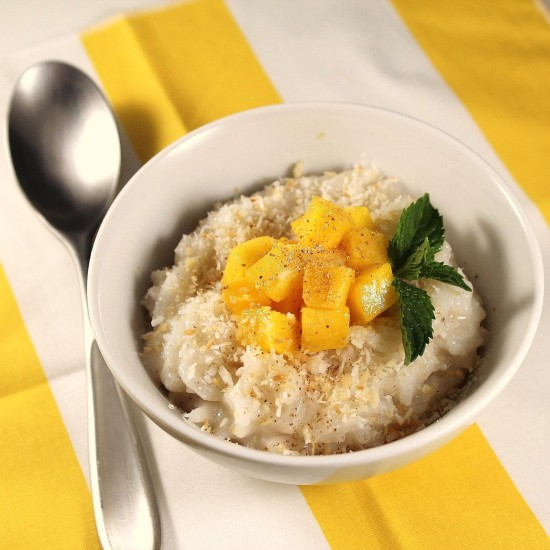 rice pudding in a white bowl with mango and toasted coconut