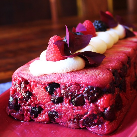 An Italian Summer Pudding decorated with whipped cream and berries