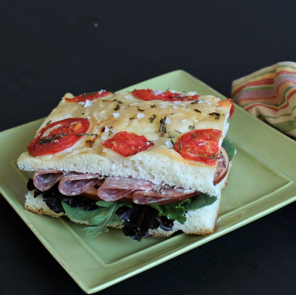 A tomato focaccia sandwich on a square green plate