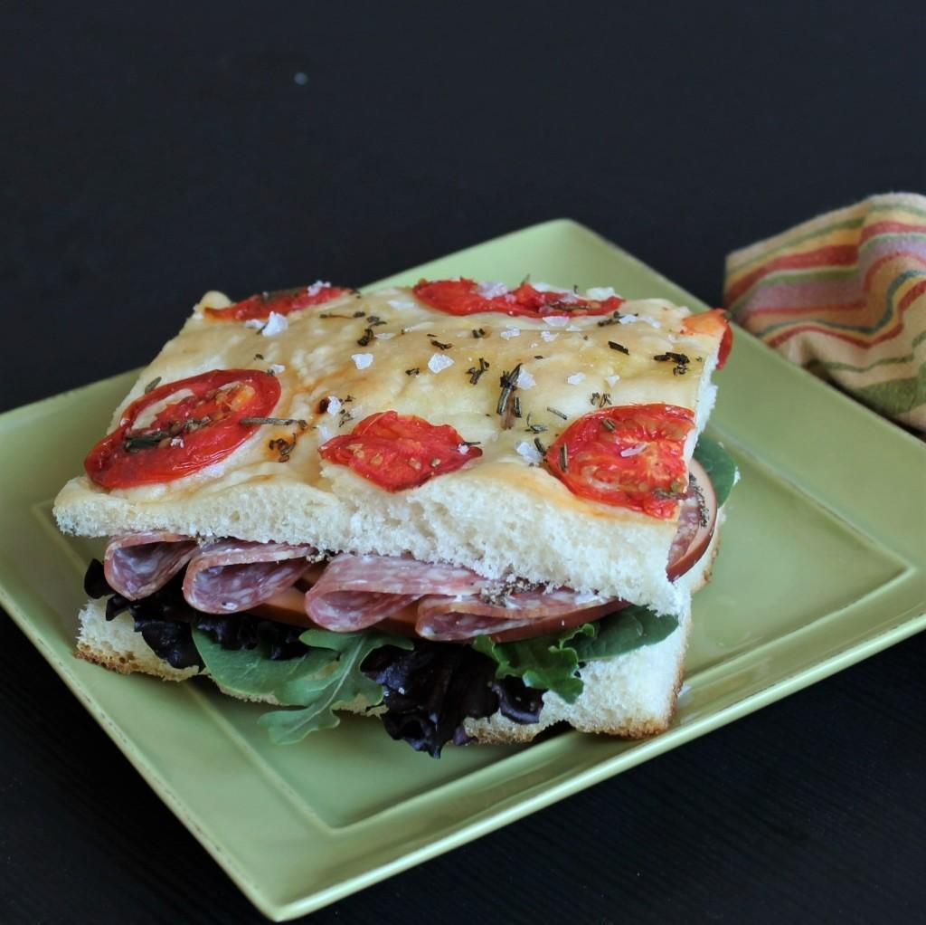 A tomato focaccia sandwich on a square green plate