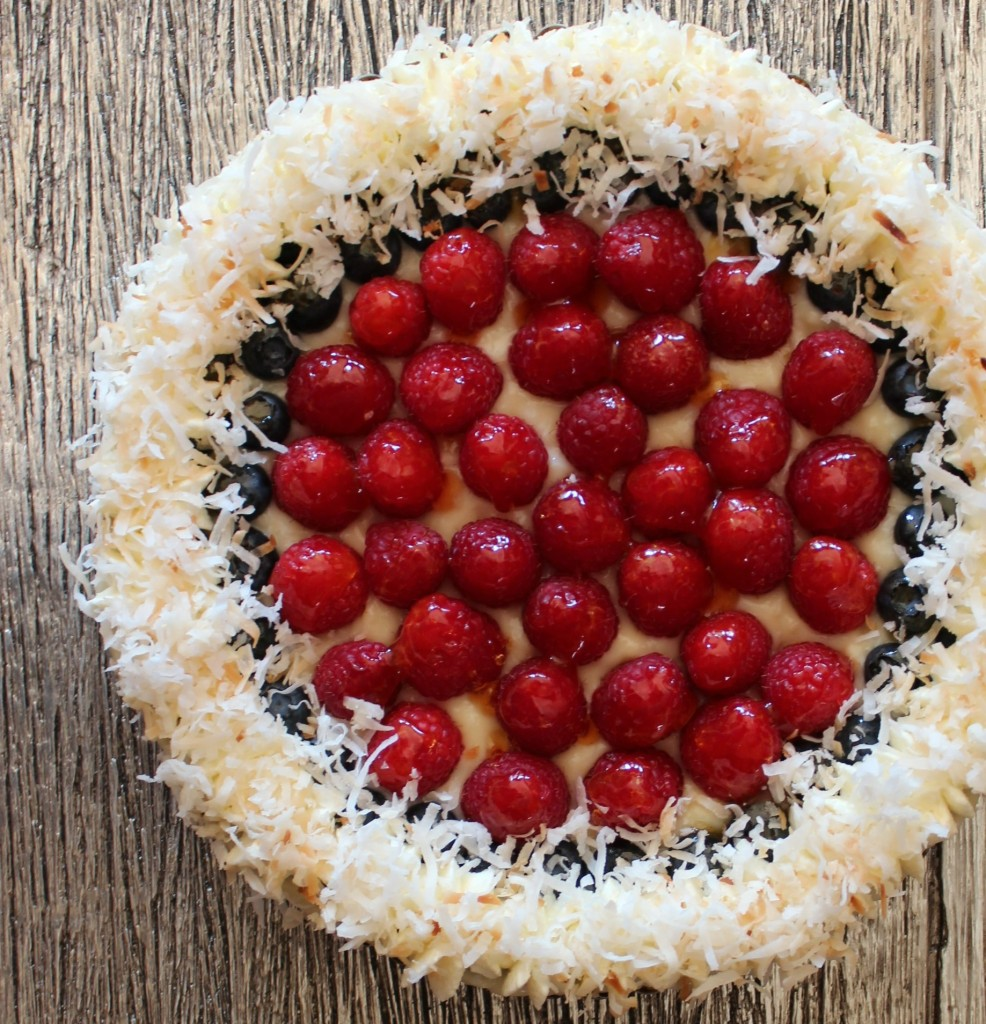 A coconut tart covered in fresh berries